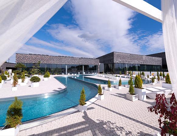 Zdjęcie przedstawia zewnętrzną część Term Warmińskich gdzie na świeżym powietrzu w basenach odbija się słońce.
