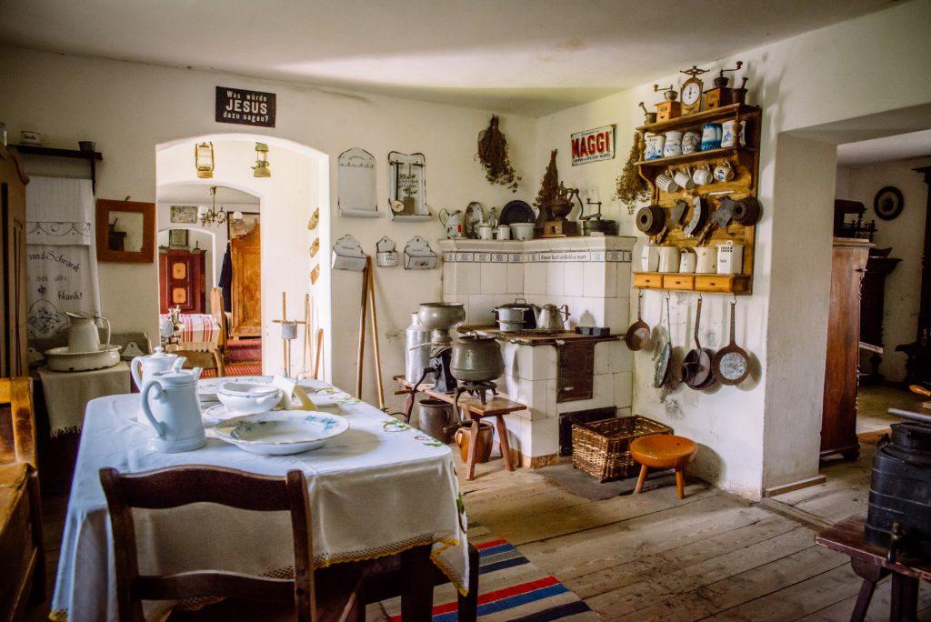 Zdjęcie przedstawia kuchenne wnętrze izby w Muzeum Mazurskim w Owczarni, gdzie na ścianach wisi dużo starodawnych przyborów, stoi pies kaflowy i stół nakryty obrusem w hafty.