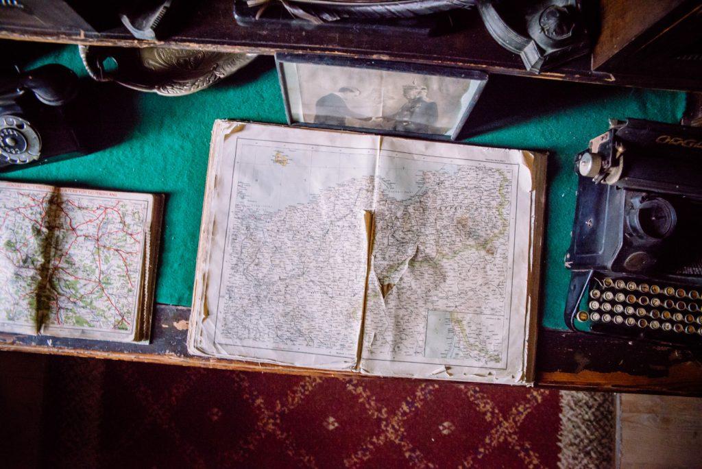 Zdjęcie przedstawia widok z góry stołu z maszyną do pisania i otwartymi starymi ugryzionymi przez ząb czasu atlasami z mapami województwa.