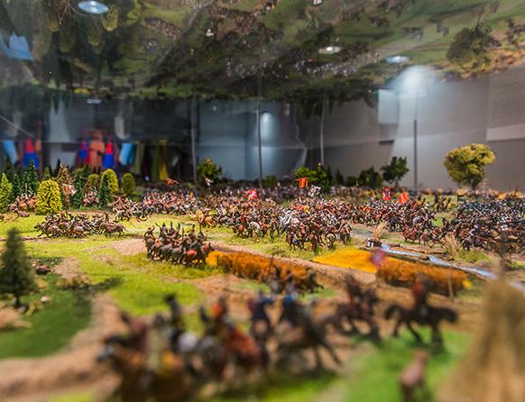 Zdjęcie przedstawia makietę w Muzeum Bitwy pod Grunwaldem, ukazującą walczących rycerzy na koniach.