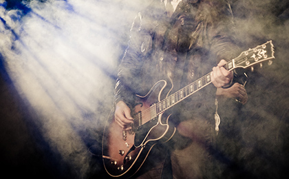 Muzyk podczas koncertu grający na gitarze, w smudze reflektorów i scenicznego sztucznego dymu.