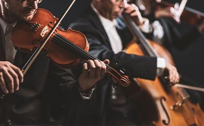 Zdjęcie przedstawia muzyków ubranych w garnitury grających koncert muzyki klasycznej na skrzypcach i wiolonczeli.