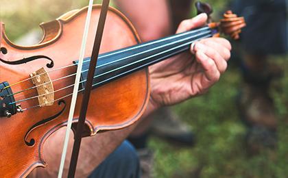 Skrzypce na których gra artysta trzymając jedną ręką smyczek a drugą instrument.