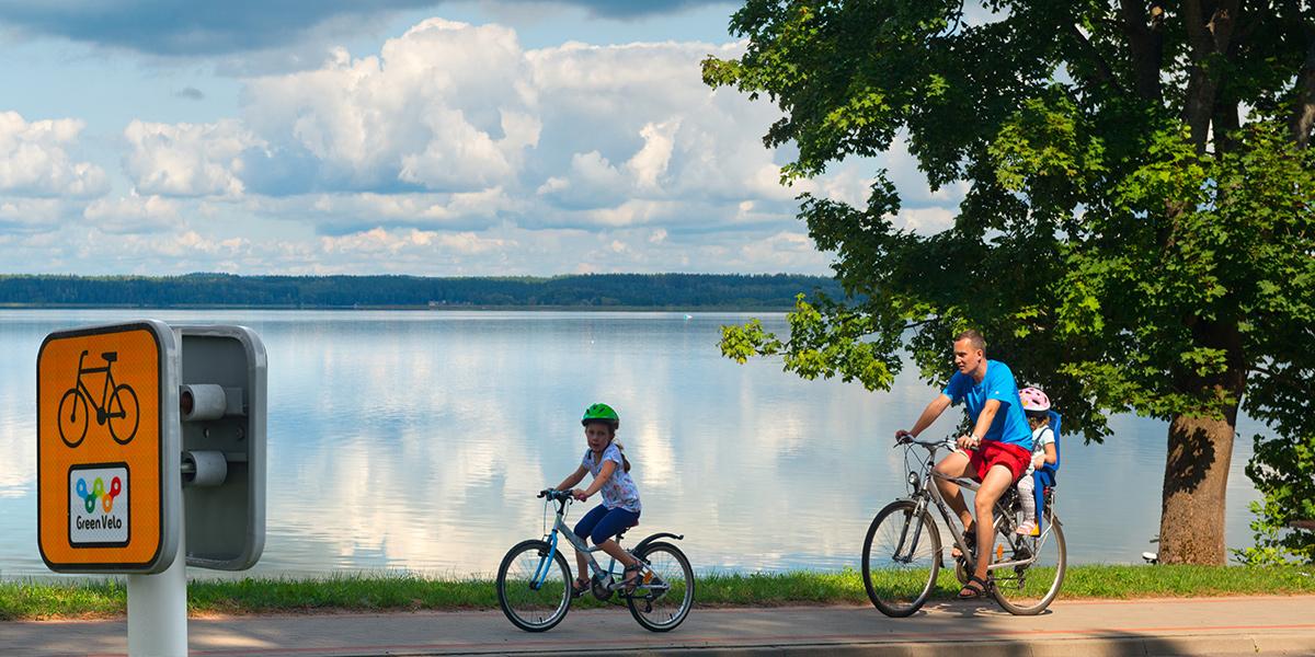Ścieżka rowerowa szlaku Green Velo na Warmii i Mazurach bezpośrednio nad jeziorem. Na ścieżce jadące dwa rowery, tata z małym dzieckiem z zamontowanym z tyłu fotelikiem oraz dziewczynka jadąca małym rowerem przed tatą.