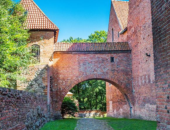 Zdjęcie przedstawia murowany Zamek Biskupów Warmińskich w Reszlu, a dokładnie łuk pod którym biegnie kamienna ścieżka dookoła której widnieje trawnik.