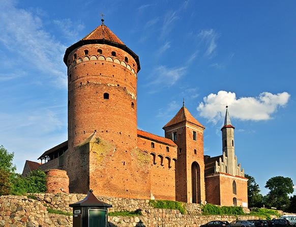 Zdjęcie przedstawia murowany Zamek w Reszlu w skład którego wchodzi wysoka wieża o okrągłym przekroju, oraz dwie mniejsze o przekrojach kolejno kwadratu i sześciokąta.