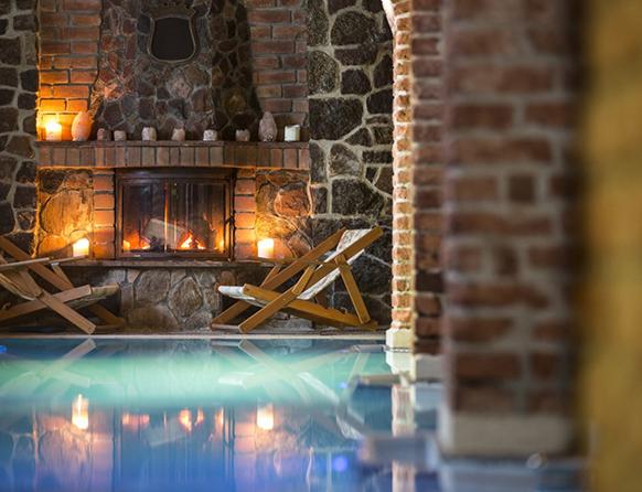 Na pierwszym planie zdjęcie ukazuje basen będący częścią SPA w Zamku Ryn. Niebieska woda prowadzi do dwóch drewnianych leżaków, za którymi w kominku pali się drewno, a na murowanym z kamieni kominku ustawione są dodatkowo palące się świece.
