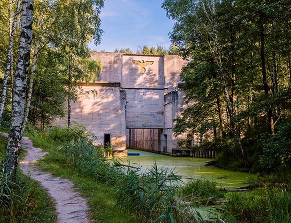 Zdjęcie przedstawia zielony las wraz z leniwie płynącą rzeką z soczyście zieloną rzęsą wodną, a nad wodą znajduje się potężnych rozmiarów betonowa brama prowadząca do bunkrów i schronów – Kwatery Główna Niemieckich Wojsk Lądowych Rzeszy w Mamerkach. Pośrodku bramy znajduje się głębienie na nazistowską gapę, czyli herb Niemiec z czarnym orłem.