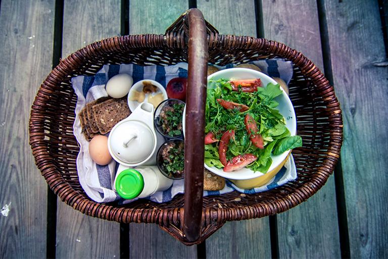 Zdjęcie przedstawia wiklinowy kosz stojący na pomoście. Zdjęcie wykonane jest z góry, ukazując w koszu sałatkę z zielonych sałat i pomidorów, jajka ugotowane na twardo, pieczywo oraz biały dzbanuszek.