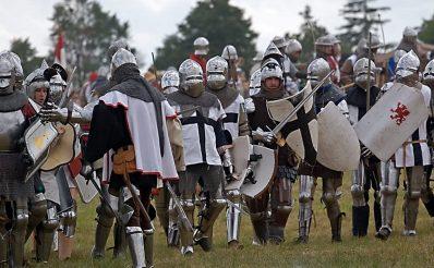 Zdjęcie zapraszające do Grunwaldu na 13 edycję Inscenizacji Bitwy pod Grunwaldem 2020. Na zdjęciu widzimy rycerzy ubranych w zbroje i stroje krzyżaków na polu bitwy pod Grunwaldem.