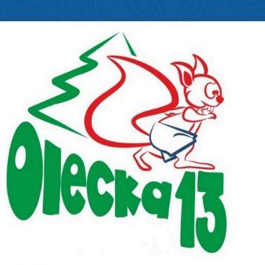 Plakat zapraszający do Olecka na 8. edycję Oleckiej Trzynastki. Grafika przedstawia napis Olecka trzynastka oraz graficzny rysunek wiewiórki.
