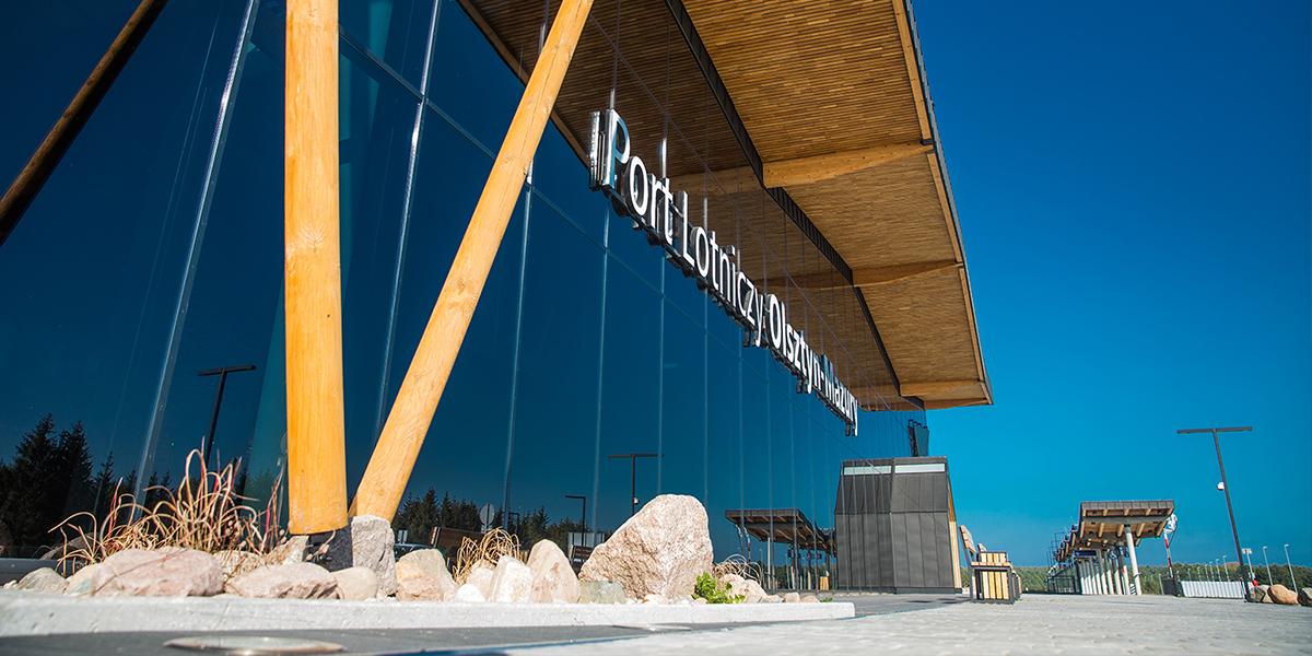 Zdjęcie przedstawia elewację wejściową Portu Lotniczego Olsztyn-Mazury. Elewacja wykonana jest ze szkła, a drewniany dach wspierają  ukośnie biegnące filary również z drewna.