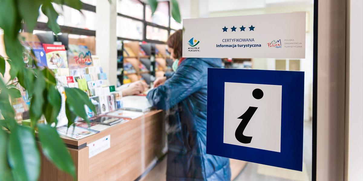 Zdjęcie przedstawia informację turystyczną, a zrobione jest zza szklanego wejścia. W środku informacji przy ladzie na której wystawione są liczne ulotki, stoi kobieta w błękitnej kurtce. Na drzwiach naklejona jest naklejka z napisem Certyfikowana Informacja Turystyczna.