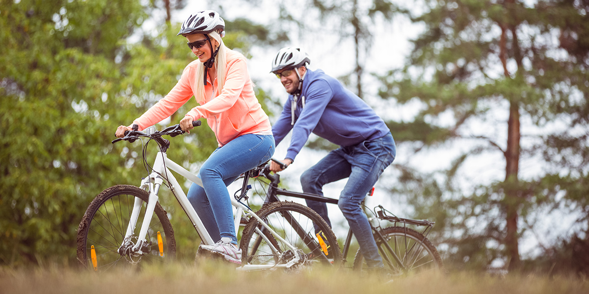 Para rowerzystów w kaskach, jadących latem ścieżką po lesie.