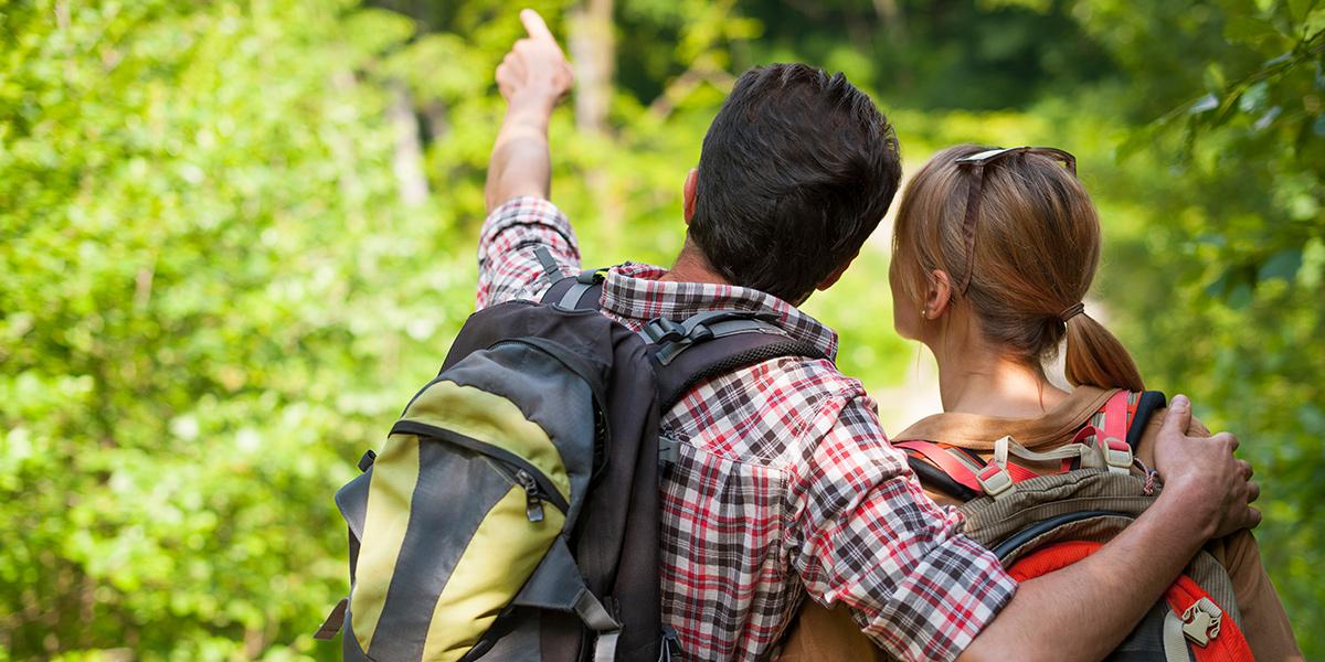 Para wędrowców spacerująca po lesie z plecakami, kobieta i mężczyzna, który obejmuje partnerkę i wskazuje palcem ciekawe miejsce w lesie. Obie osoby odwrócone są tyłem do frontu zdjęcia.
