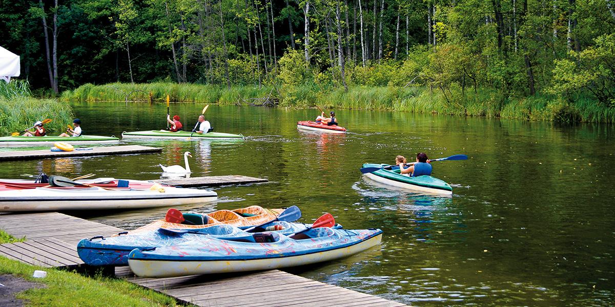 Przystań kajakowa na rzece Krutyni z drewnianym pomostem z przycumowanymi czterema kajaki. Przy przystani przepływający kajakarze udający się w dół rzeki.