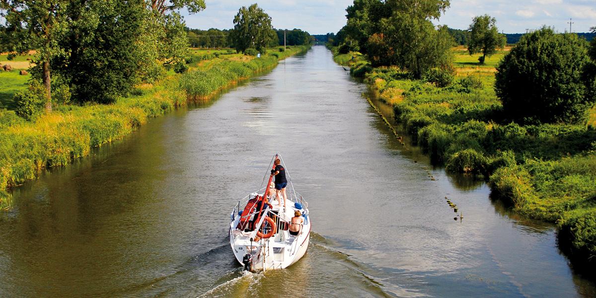 Kanał mazurski po którym płynie ze zwiniętymi żaglami i na silniku żaglówka. Po obu stronach kanału pola i łąki.