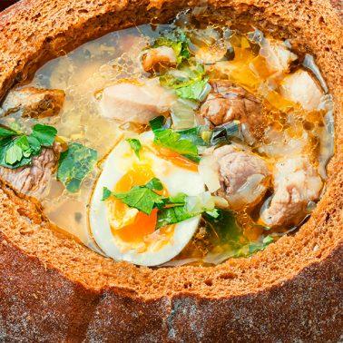 Zdjęcie ilustracja przedstawiające zupę danie mazurskie podane w bochenku chleba.