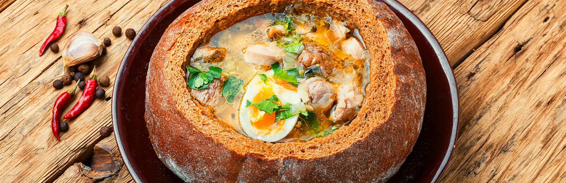 Zupa mięsna z jajkiem i włoszczyzną, podane wewnątrz okrągłego bochenka chleba. Danie mazurskie podane na stole w żeliwnej misce.