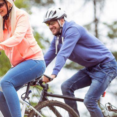 Zdjęcie - ilustracja przedstawiająca dwóch rowerzystów jadących ścieżką po lesie.
