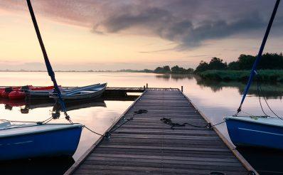 Pomost na mazurskim jeziorze do którego przycumowane są żaglówki w trakcie pochmurnej pogody i  zachodzącego słońca.