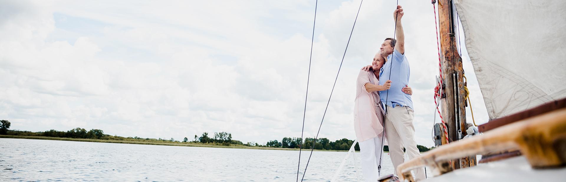 Zdjęcie - ilustracja przedstawiająca parę żeglarzy pływających na żaglówce po mazurskich jeziorach.