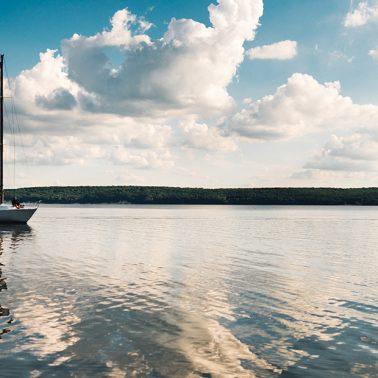 Zdjęcie ilustracja przedstawiająca płynącą żaglówkę po jeziorze mazurskim.