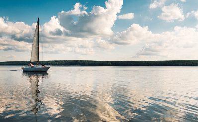 Samotna żaglówka pływającą po spokojnym mazurskim jeziorze.