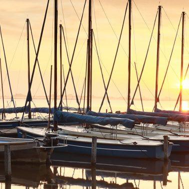 Zdjęcie ilustracja przedstawiająca żaglówki przycumowane przy pomoście podczas zachodu słońca.