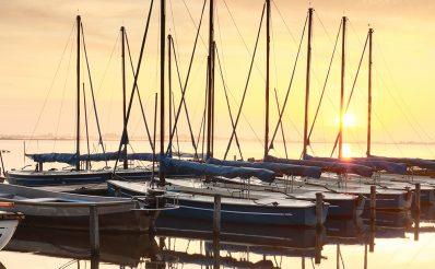 Przycumowane stojące w szeregu żaglówki na mazurskim jeziorze w podczas wschodu słońca.