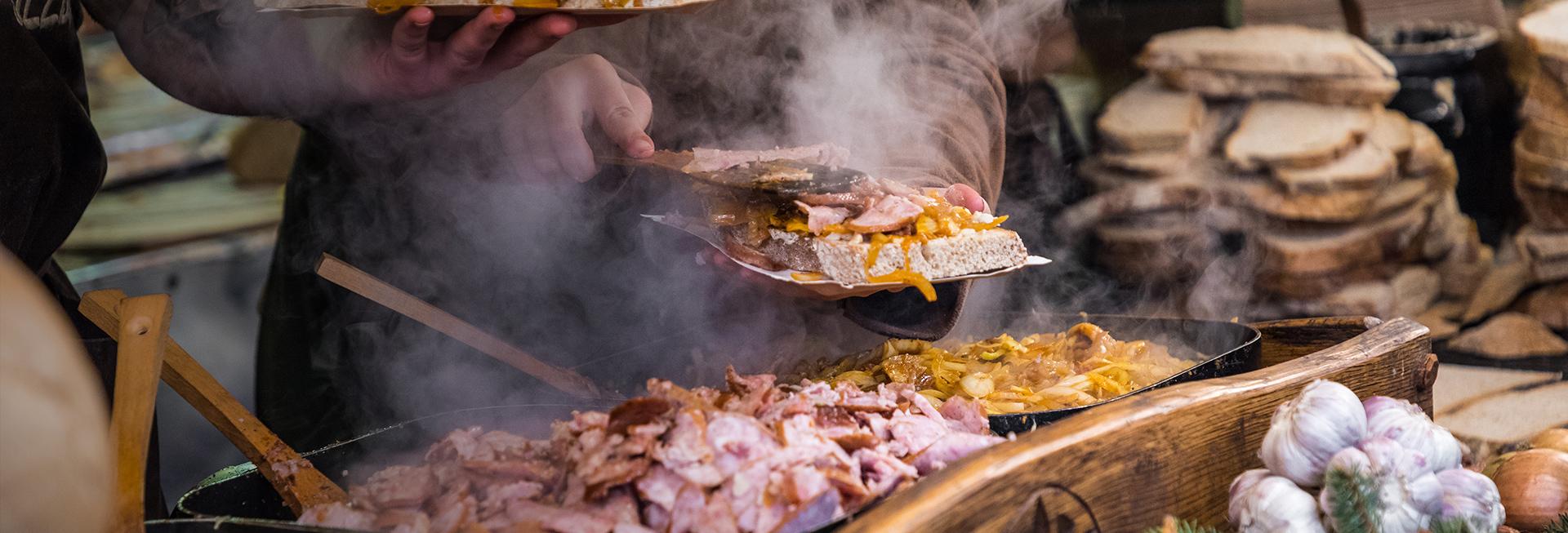 Biesiada mazurska, podczas której dwie osoby nakładają na chleb porcję pieczonego mięsa, cebuli i duszonych warzyw. Obok gorących patelni na stole znajdują się porcje chleba, masła oraz ząbki czosnku.