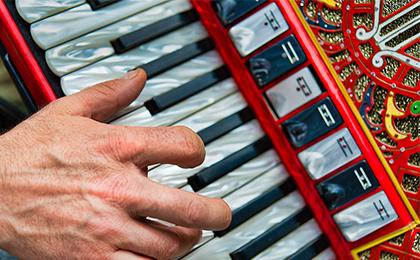 Akordeon bogato zdobiony na którym gra artysta, trzymając rękę na klawiaturze instrumentu.