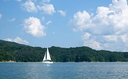 Zdjęcie - ilustracja przedstawiająca żaglówkę pływającą po mazurskich jeziorach.