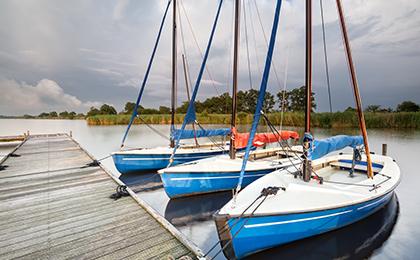 Przycumowane do pomostu na mazurskim jeziorze stojące w szeregu trzy żaglówki podczas pochmurnej pogody.