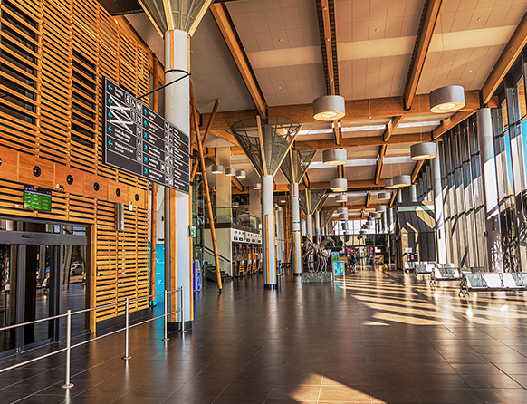 Zdjęcie przedstawia wnętrze lotniska w Szymanach. Wysoka hala ma dużo elementów z jasnego drewna, którym wyłożone są ściany i sufit. na środku zdjęcia znajduje się drogowskaz dla podróżnych.