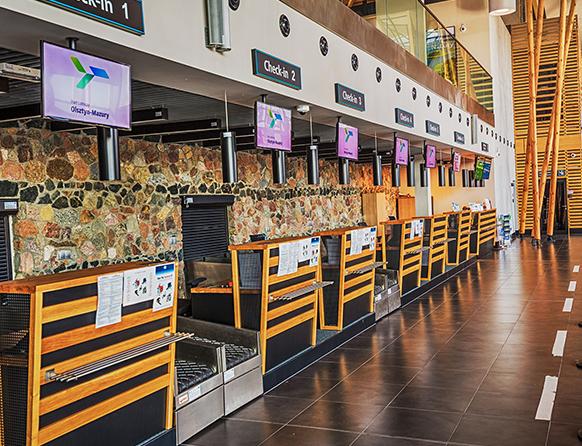 Zdjęcie przedstawia lotnisko w Szymanach, a dokładnie miejsca odprawy podróżników. Kilka stanowisk z czarnymi taśmami na które podróżni oddają bagaże są odgrodzone od reszty hali białą przerywaną linią namalowaną na czarnej podłodze.