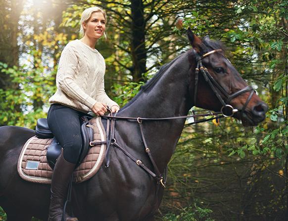 Kobieta siedząca w siodle na koniu będąca w mazurskim lesie w trakcie turystycznej przejażdżki konnej.