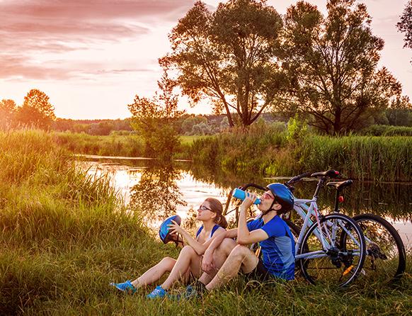 Para rowerzystów odpoczywa, siedząc przy rowerach i pijąc wodę z bidonu nad brzegiem rzeki Krutynia.