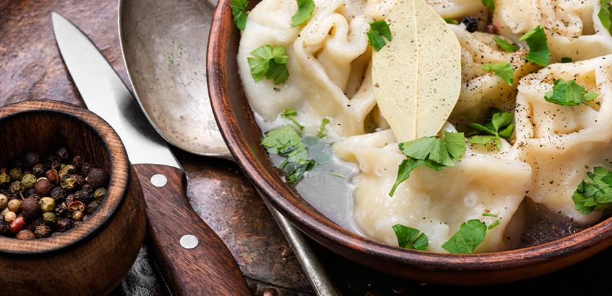 Zdjęcie przedstawia danie regionalnej kuchni warmińsko-mazurskiej czyli dzyndzałki w rosole posypane przyprawami i przyozdobione pietruszką.