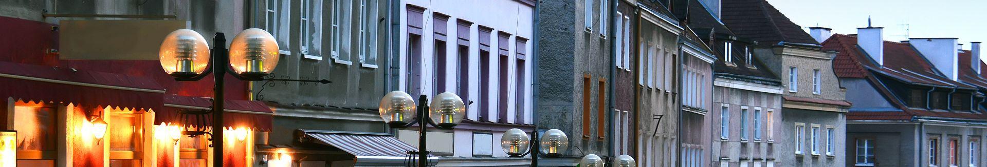 Zdjęcie przedstawia rząd budynków przy ulicy Prostej na olsztyńskim starym mieście. Kamienice mają różne wysokości, kolory elewacji i formy budowy.