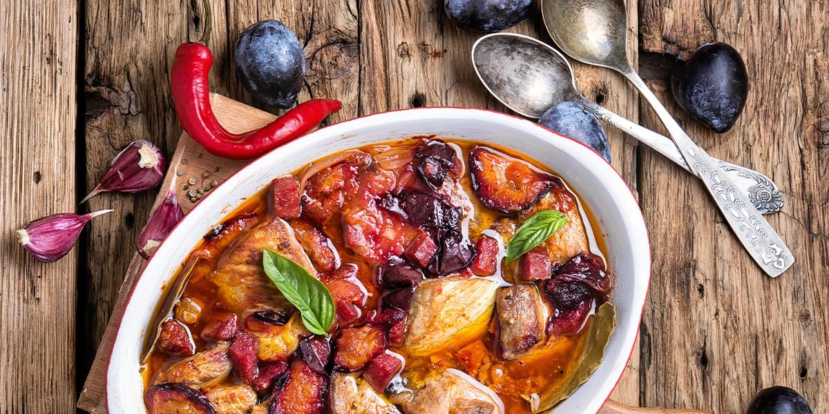 Micha a w niej potrawa z dziczyzny w której znajdziemy mięso, ziemniaki, warzywa, włoszczyznę a wszystko to przyprawione własnym sosem. Obok glinianej michy dwie łyżki, czosnek, czerwona papryczka i mazurskie śliwki.