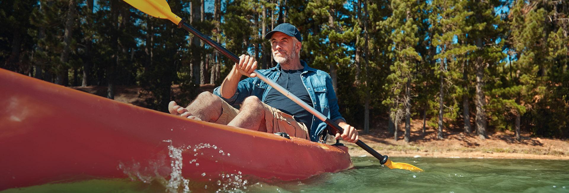 Samotny turysta płynący kajakiem po mazurskiej rzece, blisko brzegu porośniętego drzewami.
