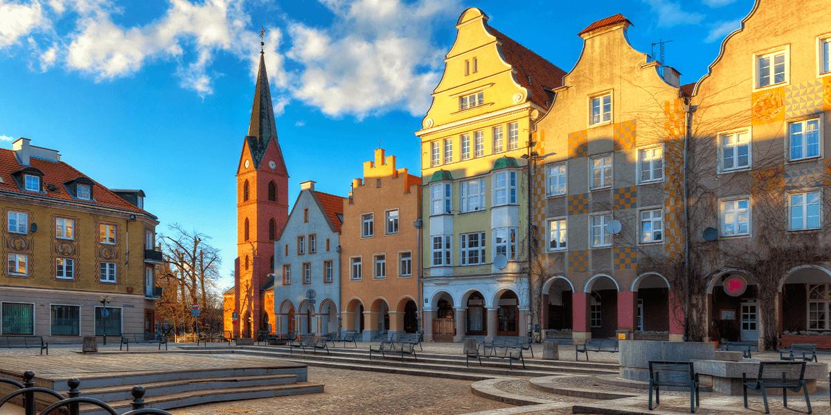 Plac na Starówce oraz zabytkowe budynki Starówki Miejskiej w Olsztynie podczas zachodzącego słońca.