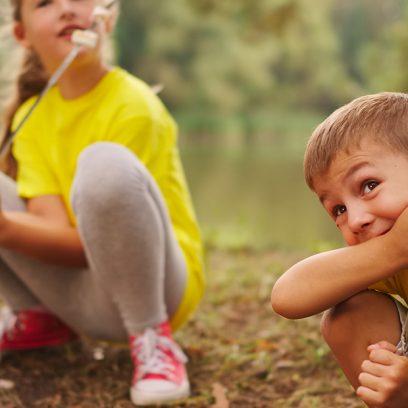 Na zdjęciu mała dziewczynka i chłopiec bawiące się w lesie.