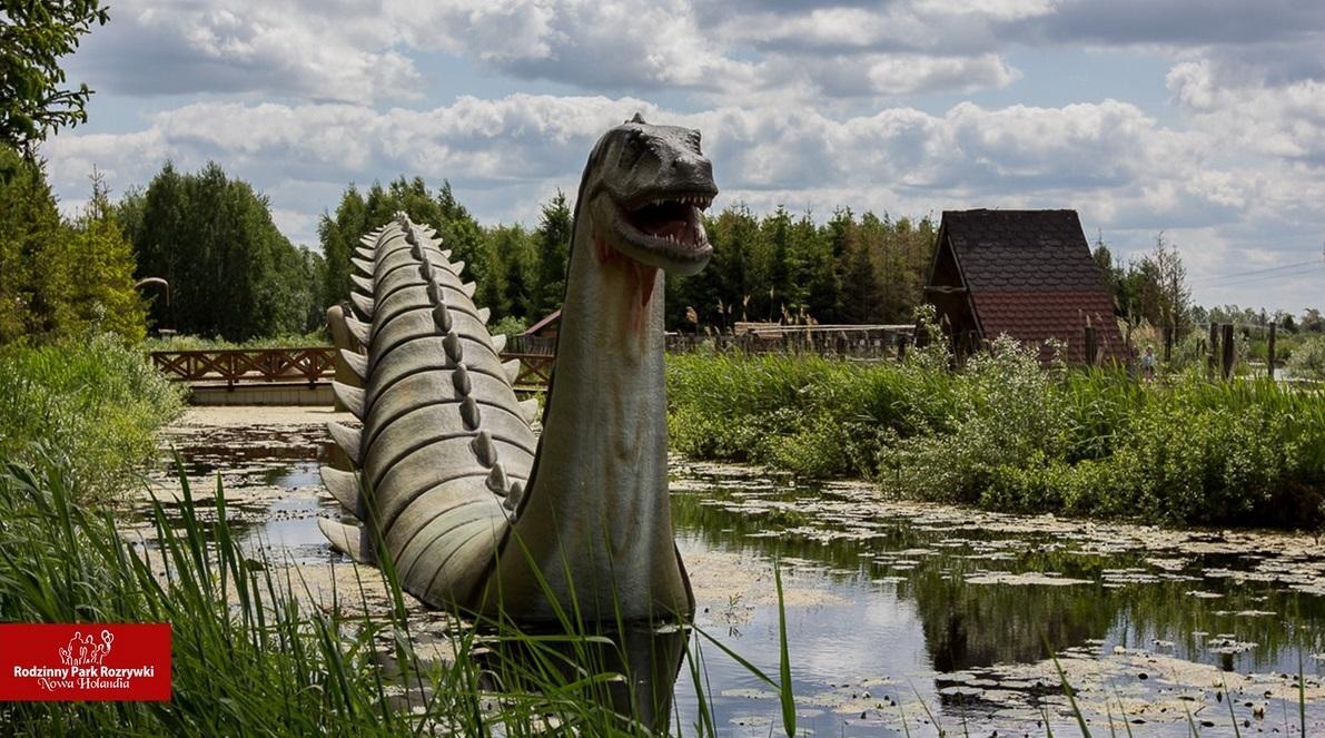 Rodzinny Park Rozrywki Nowa Holandia. Na zdjęciu widoczna replika dinozaura zanurzonego w wodzie po środku stawu.
