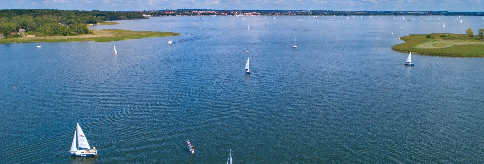 Jezioro z lotu ptaka na widoczne są pływające żaglówki. Na dalszym planie widzimy przesmyk pomiędzy akwenami porośnięty z obu stron trzciną.