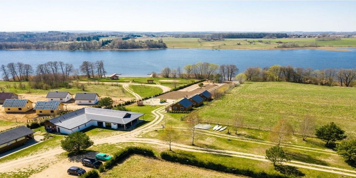 Widok z lotu ptaka ośrodka i campingu Pajda Mazur w miejscowości Kątno. Ośrodek położony z bezpośrednim dostępem do jeziora. Na ogrodzonym polu, camping, domki letniskowe oraz budynki gospodarcze. W tle jezioro z dwoma pomostami.