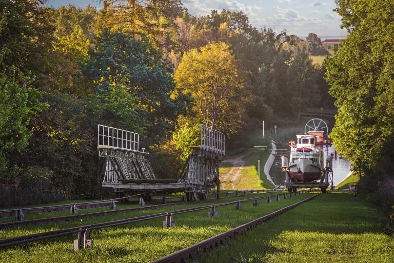 Kanał Ostródzko-Elbląski. Na zdjęciu pusty wózek na torowisku do załadunku statku na szlaku kanału żeglugi. Poniżej w tle wózka pusta pochylnia oraz druga pochylnia z załadowanym statkiem.