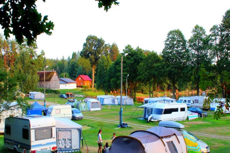Panorama campingu Dłużek na której widzimy rozstawione na polu biwakowym namioty, przyczepy oraz zaparkowane campery nad brzegiem jeziora.