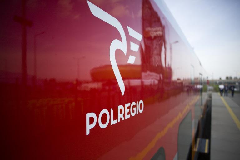 Zdjęcie z bardzo bliska loga POLREGIO, widocznego na wagonie pociągu, stojącego na peronie dworca PKP.